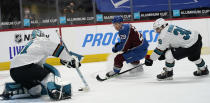 Colorado Avalanche center Nathan MacKinnon, center, drives past San Jose Sharks defenseman Mario Ferraro, right, after putting a shot on goaltender Martin Jones during the first period of an NHL hockey game Tuesday, Jan. 26, 2021, in Denver. (AP Photo/David Zalubowski)