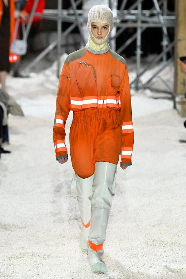 <p>A model wears a cropped orange safety jacket and trousers with reflective panels, a balaclava, and thigh-high white protective boots at the Calvin Klein fall 2018 show. (Photo: Getty Images) </p>