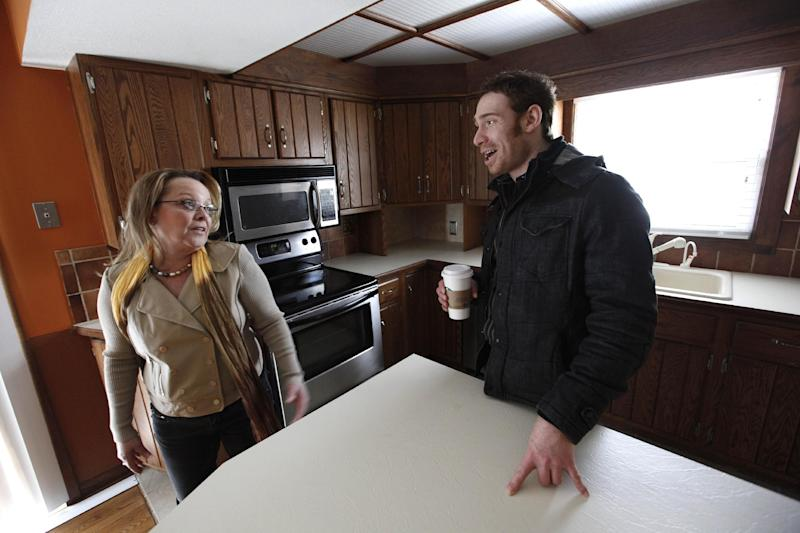 In this Tuesday, April 2, 2013 photo, real estate agent Michelle Gordon, left, talks with client Michael Weitzman while viewing a home for sale in Grand Rapids, Mich. The American economy and job market are moving in the right direction, just not very quickly. The news Friday, May 3, 2013, that U.S. employers added a solid 165,000 jobs in April and unemployment fell to a four-year low 7.5 percent came as a relief. Fueled by near-record low mortgage rates, the housing market has been bouncing back. New-home sales in March were up 18.5 percent from a year earlier. Sales of previously occupied homes were up 10.3 percent. For the first time in five years, homebuilders started work on more than 1 million homes in March at a seasonally adjusted annual rate. (AP Photo/Paul Sancya)