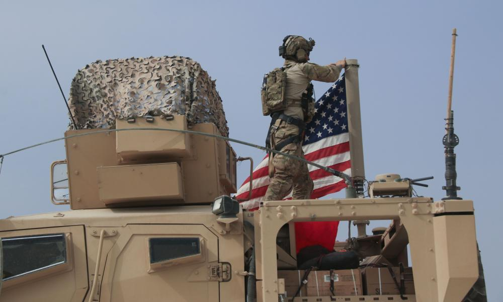 """<span class=""""element-image__caption"""">An American soldier mounts the US flag on a vehicle near the town of Tel Tamr in northern Syria.</span> <span class=""""element-image__credit"""">Photograph: Baderkhan Ahmad/AP</span>"""