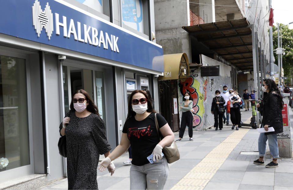 People wearing face masks for protection against the coronavirus, walk in Ankara, Turkey, Monday, May 11, 2020. Shopping malls, barber shops, hairdressers and beauty salons have reopened for business across Turkey for the first time in seven weeks as the country gradually eases restrictions aimed to prevent the spread of the new coronavirus.(AP Photo/Burhan Ozbilici)