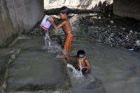 Boys bathe at concrete water pens to cool off under a flyover in a slum area on a hot summer day in Kolkata, India, April 27, 2016. REUTERS/Rupak De Chowdhuri