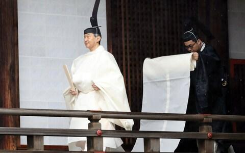 In an earlier ceremony the Emperor and Empress wore multi-layered white robes - Credit: REX