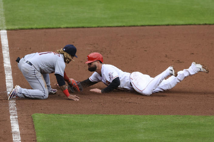 Cleveland Indians' Jose Ramirez, left, tags out Cincinnati Reds' Jesse Winker who was attempting to steal third base during the seventh inning of a baseball game in Cincinnati, Saturday, April 17, 2021. (AP Photo/Aaron Doster)