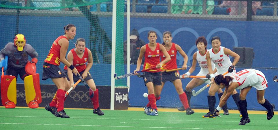 Chen Qiuqi (R) of China hits a ball as Spain players look on during their 2008 Olympics Games women's field hockey match in Beijing on August 10, 2008. China won 3-0.   AFP PHOTO/ AAMIR QURESHI                  (Photo credit should read AAMIR QURESHI/AFP via Getty Images)