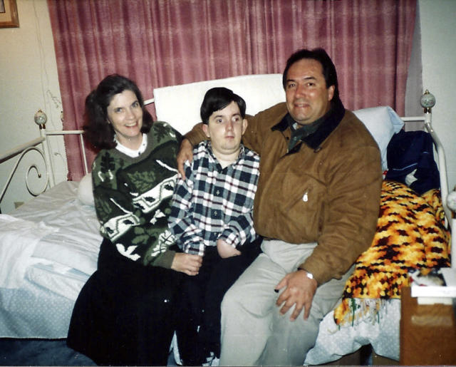This undated handout photo provided by Paul Cortez shows 15-year-old Mikey Cortez, center, and his parents, Paul and Roonie Cortez. As his 7-year-old son Mikey lay in a hospital bed on life support, the victim of a drunk driver who had smashed into the car he was riding in, Paul Cortez took the boy's hand and made a solemn promise to God: If his son survived, no matter in what condition, he and his family would always be there for him. Although he would never emerge from the persistent vegetative state his father had found him in that night, Mikey's family was not only there for him but also gave him a full life. A life, as it turned out, not all that different from anybody else's, with cross-country family vacations and visits to Disneyland.(AP Photo/Courtesy Cortez Family)