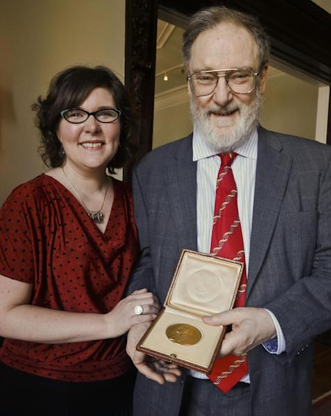 Kendra Crick pose with her father Michael Crick as he holds the 1962 Nobel Prize for Medicine awarded to his father Dr. Francis Harry Compton Crick, Wednesday, April 10, 2013 in New York. On Thursday, the molecular biologist's 1962 Nobel Prize medal in physiology or medicine and diploma will be sold by Heritage Auctions, which estimates it could fetch at least $500,000. (AP Photo/Bebeto Matthews)