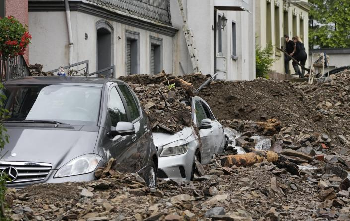 Cars in Hagen, Germany, on Thursday are covered by debris from the flooding of the River Volme.