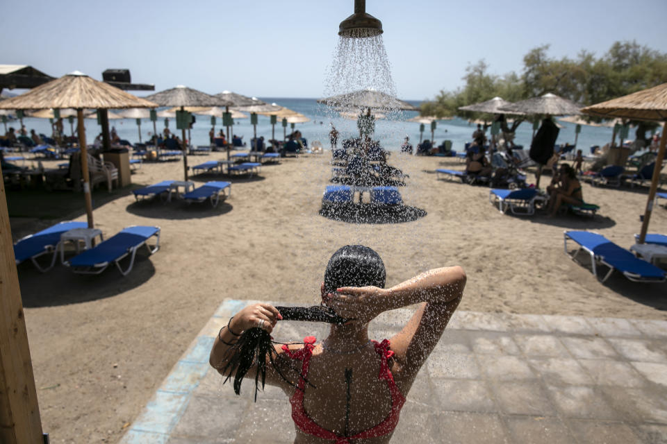 A woman takes a shower at a beach of Lagonissi village, a few miles southwest of Athens, on Thursday, July 29, 2021. One of the most severe heat waves recorded since 1980s scorched southeast Europe on Thursday, sending residents flocking to the coast, public fountains and air-conditioned locations to find some relief, with temperatures rose above 40 C (104 F) in parts of Greece and across much of the region. (AP Photo/Yorgos Karahalis)