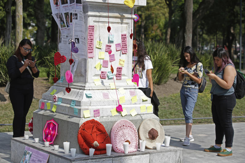 Women write the names of victims on post-it notes during a tribute for murdered women, in the Alameda park of Mexico City, Saturday, Aug. 24, 2019. A small group of women constructed a memorial made of hand-knit hearts. The knit-in on came on the heels of rowdy protests sparked by outrage over bungled investigations into alleged rapes of teenagers by local policemen. (AP Photo/Ginnette Riquelme)