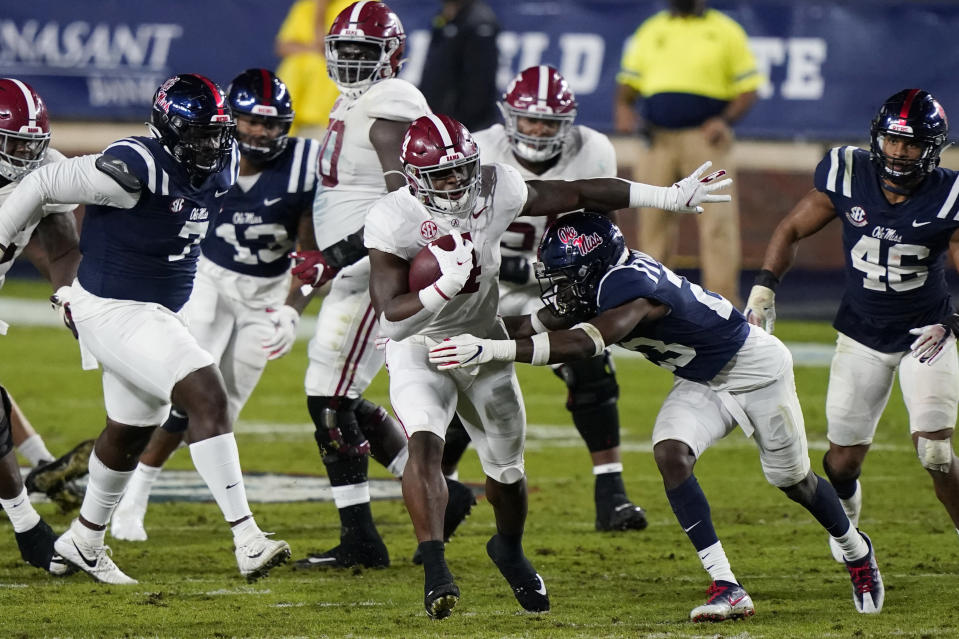 Alabama running back Brian Robinson Jr. (4) runs between Mississippi defenders, including defensive back Jakorey Hawkins (23), during the first half of an NCAA college football game in Oxford, Miss., Saturday, Oct. 10, 2020. (AP Photo/Rogelio V. Solis)