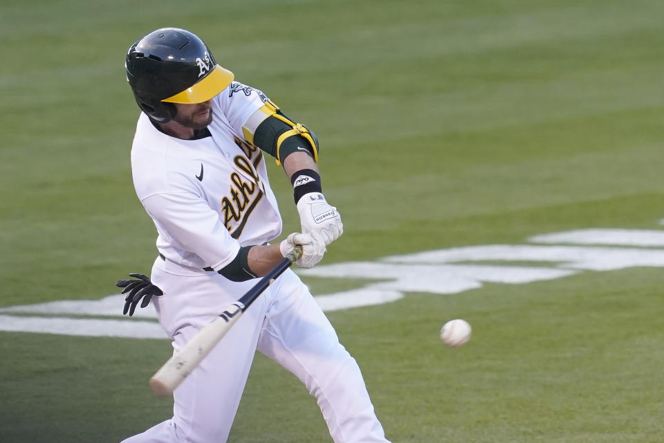 Oakland Athletics' Jed Lowrie hits a two-run double against the Toronto Blue Jays during the second inning of a baseball game in Oakland, Calif., Tuesday, May 4, 2021. (AP Photo/Jeff Chiu)
