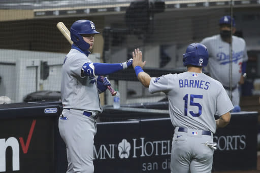Los Angeles Dodgers' Joc Pederson high-fives Austin Barnes after he scored on a fielder's choice against the San Diego Padres in the third inning of a baseball game Monday, Sept. 14, 2020, in San Diego. Dodgers Corey Seager grounded out to second base on the play. (AP Photo/Derrick Tuskan)