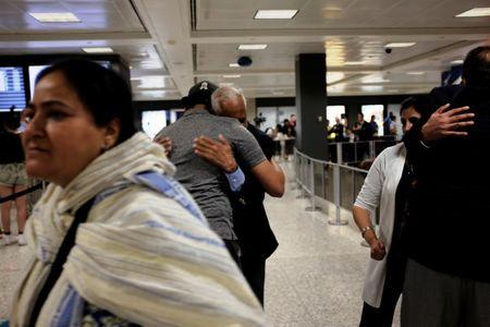 International passengers embrace family members as they arrive at Washington Dulles International Airport after the Trump administration's travel ban was allowed back into effect pending further judicial review, in Dulles, Virginia