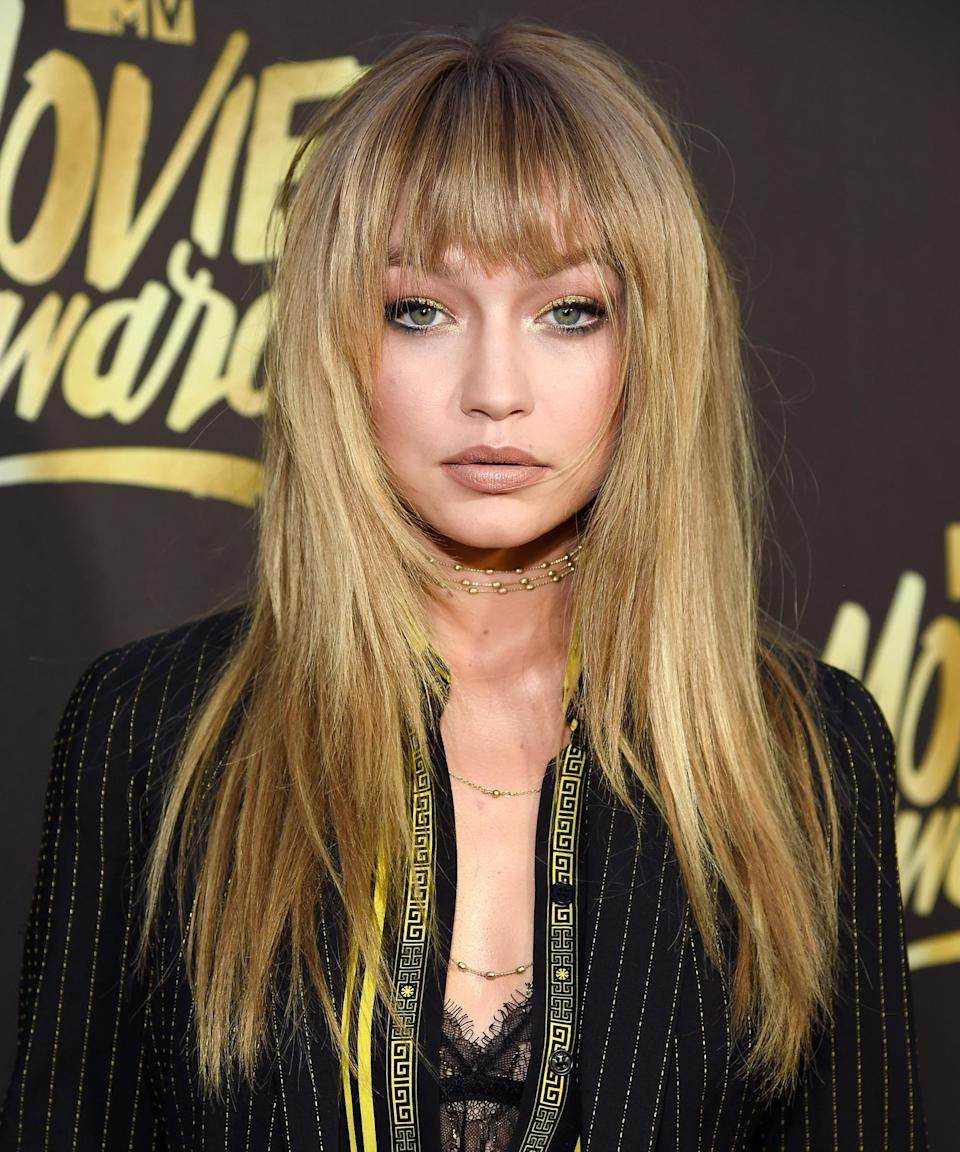 """<h3>2016</h3> <br><br>Gigi loves faking out fans with temporary hair, as evidenced by her <a href=""""https://www.refinery29.com/en-us/2016/10/127226/how-to-style-fake-bangs-hair-trend-tutorial"""" rel=""""nofollow noopener"""" target=""""_blank"""" data-ylk=""""slk:clip-in bangs"""" class=""""link rapid-noclick-resp"""">clip-in bangs</a> at the 2016 MTV Movie Awards. Despite their authenticity, or lack thereof, there's no doubt that the messy bedhead vibe is one Gigi wears well.<span class=""""copyright"""">Photo: Kevin Mazur/WireImage.</span><br><br>"""