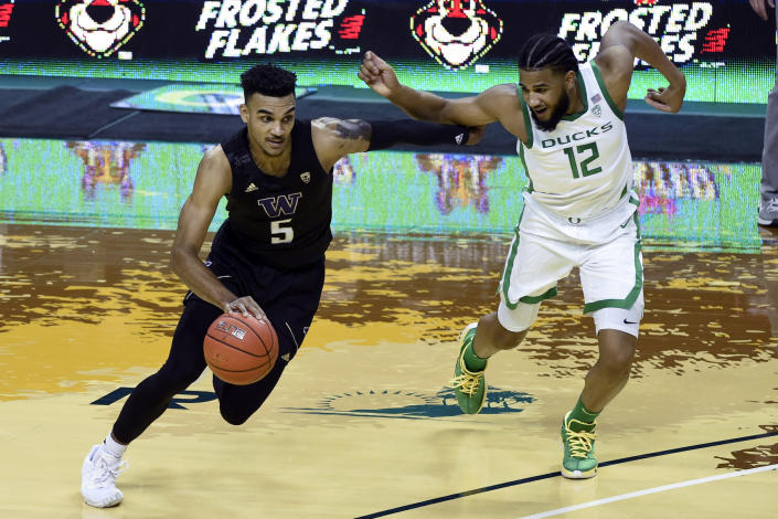 Washington guard Jamal Bey (5) drives past Oregon guard LJ Figueroa (12) during the first half of an NCAA college basketball game Saturday, Feb. 6, 2021, in Eugene, Ore. (AP Photo/Andy Nelson)