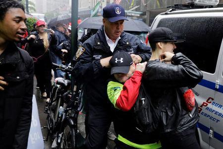 A New York Police Department officer attempts to break up a fight between a demonstrator (C) who had been protesting against CUNY's decision to allow Linda Sarsour, a liberal, Palestinian-American political activist, to speak at this year's commencement and an anti-Trump demonstrator during a scuffle in New York, U.S., May 25, 2017. REUTERS/Lucas Jackson