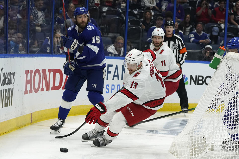Carolina Hurricanes left wing Warren Foegele (13) intercepts a pass by Tampa Bay Lightning right wing Barclay Goodrow (19) during the first period in Game 3 of an NHL hockey Stanley Cup second-round playoff series Thursday, June 3, 2021, in Tampa, Fla. (AP Photo/Chris O'Meara)