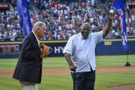 Hank Aaron holds up the ball after throwing the ceremonial last pitch to former Manager Bobby Cox after a baseball game against the Detroit Tigers and the Braves last game at Turner Field, Oct. 2, 2016, in Atlanta. (AP Photo/John Amis)