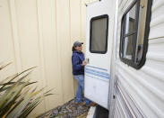 Melynda Small walks into a the trailer she is living in in the parking lot of a Comfort Inn in Lincoln City, Ore., on Thursday, May. 13, 2020. Small has dedicated her time to helping the small Oregon coast town of Otis recover from the devastating fire that destroyed 293 homes. She is living in the trailer while her four children live in the hotel. Experts say the 2020 wildfire season in Oregon was a taste of what lies ahead as climate change makes blazes more likely and more destructive even in wetter, cooler climates like the Pacific Northwest. (AP Photo/Craig Mitchelldyer)