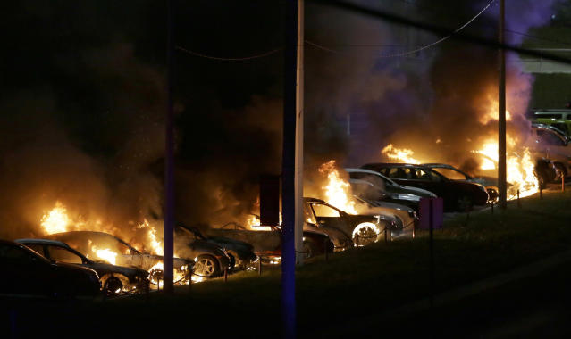 <p>Cars burn at a dealership Tuesday, Nov. 25, 2014, in Dellwood, Mo. A grand jury has decided not to indict Ferguson police officer Darren Wilson in the death of Michael Brown, the unarmed, black 18-year-old whose fatal shooting sparked sometimes violent protests. (AP Photo/Charlie Riedel) </p>