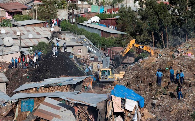 Excavators move earth as rescuers work at the site of a landslide at the main landfill of Addis Ababa - Credit: AFP