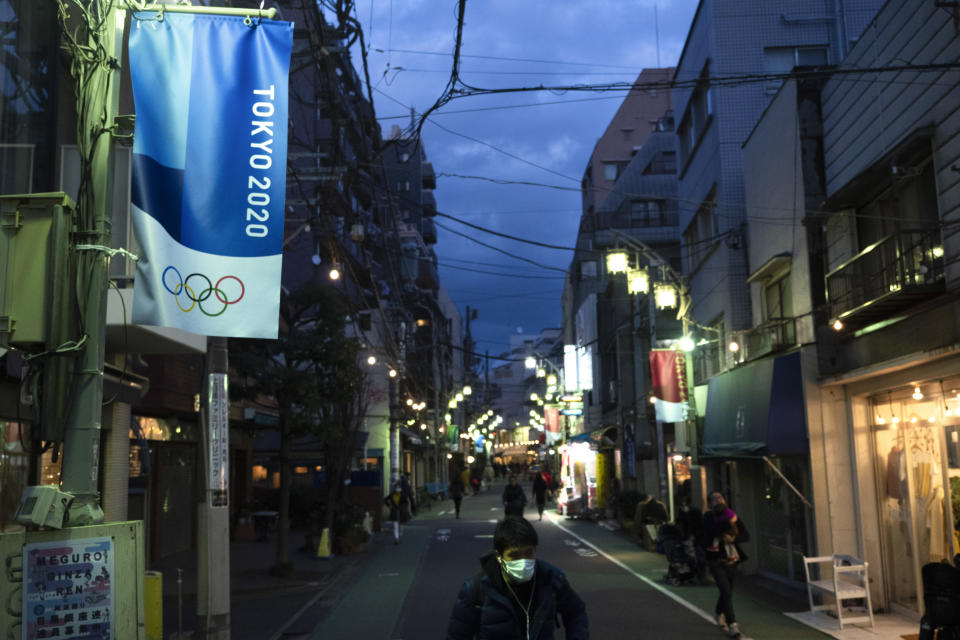 People walk along an alleyway adorned with banners promoting the Tokyo 2020 Olympics in Tokyo, Sunday, March 15, 2020. As the IOC attempts to keep the 2020 Olympics on schedule, many of the events that determine who would compete in Tokyo have been postponed or canceled. (AP Photo/Jae C. Hong)