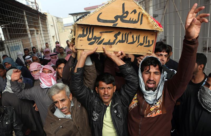 """FILE - In this file photo taken Wednesday, Nov. 27, 2013, mourners chant slogans against sectarianism while carrying the coffin of Sunni Sheik Adnan Majeed al-Ghanem during his funeral in Basra, Iraq's second-largest city, 340 miles (550 kilometers) southeast of Baghdad, Iraq. The monthly death toll in Iraq dropped by nearly a third to 659 last month, the U.N. said Sunday, but a recent spike in the number of bullet-riddled bodies found on the street has raised fears the country is facing a return to all-out warfare between Sunni and Shiite factions. The Arabic on the coffin reads, """"Al-Shati. There is no god but Allah, and Mohammed is his messenger."""" (AP Photo/Nabil al-Jurani, File)"""