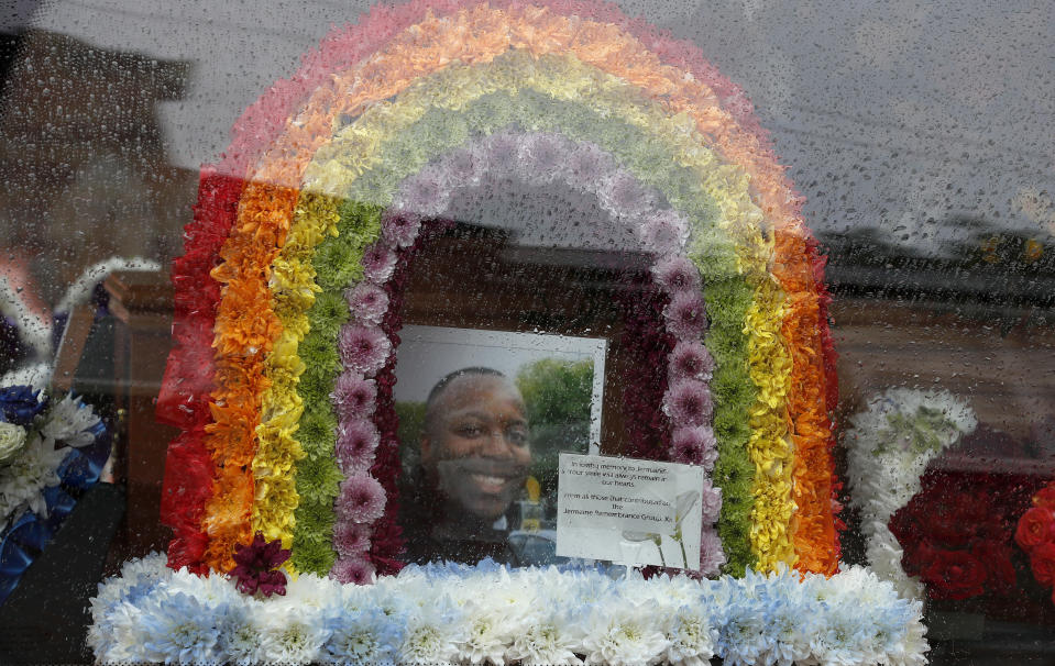 In this photo taken on Thursday, June 11, 2020, a view of photo and floral tribute for Jermaine Wright, a pharmacist and a referee of the Hackney Marshes grassroots football league, inside the hearse on the day of his funeral, in London. Wright, affectionately known as Mr. Hackney Marshes, served as both an on-field referee and a behind-the-scenes catalyst in the Hackney & Leyton Sunday Football League — as vice chairman, schedule secretary, results secretary, press officer, and head official before he died on April 27, 2020 from COVID-19. (AP Photo/Frank Augstein)