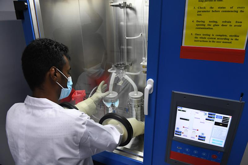 A lab technician places a face mask through a bacterial filtration efficiency tester during a media tour of a Setsco laboratory that tests surgical masks in Singapore on August 18, 2020. (Photo by ROSLAN RAHMAN / AFP) (Photo by ROSLAN RAHMAN/AFP via Getty Images)