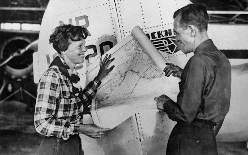Amelia Earhart, left, and navigator Fred Noonan pose with a map of the Pacific Ocean showing the planned route of their round-the-world flight - AP