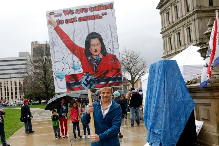 A protester holds a sign with Michigan Gov. Gretchen Whitmer depicted as Adolf Hitler at a rally on the steps of the state Capitol in Lansing on April 30. (Jeff Kowalsky/AFP via Getty Images)