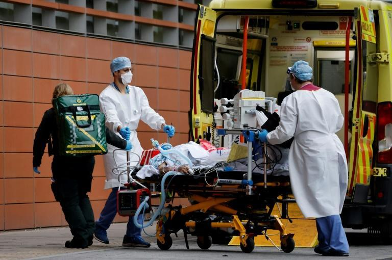 Medics take a patient from an ambulance into the Royal London hospital in London on January 19, 2021