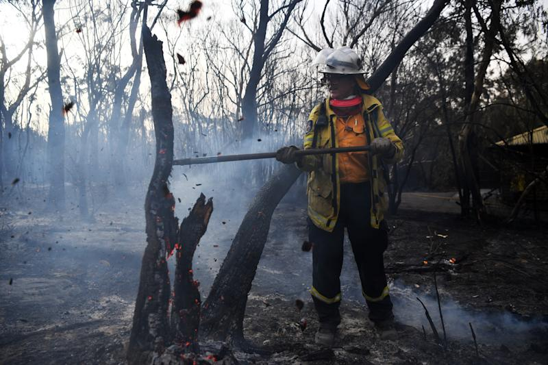 A NSW RFS firefighter undertakes mopping up at South Turramurra.