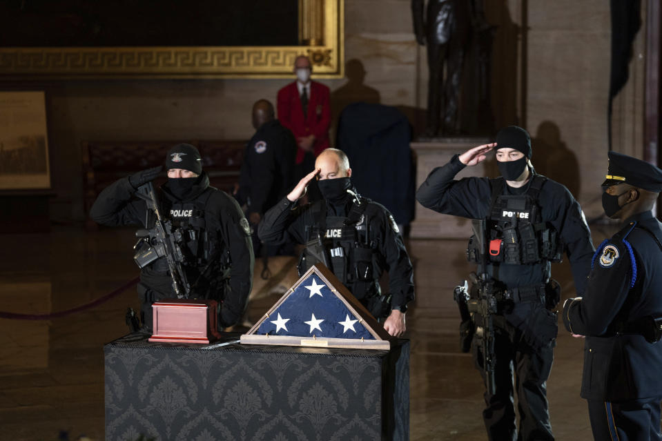FILE - In this Wednesday, Feb. 3, 2021 file photo, Capitol Police officers pay respects to the late U.S. Capitol Police officer Brian Sicknick as an urn with his cremated remains lies in honor on a black-draped table at the center of the Capitol Rotunda in Washington. On Friday, Feb. 12, 2021, The Associated Press reported on stories circulating online incorrectly asserting Fox News entirely ignored the Feb. 2 ceremony in the Capitol Rotunda honoring the slain U.S. Capitol Police officer, as television networks such as CNN and MSNBC broadcast live coverage. Fox News did not air the entire ceremony for Sicknick live on its main cable channel, but two of its hosts briefly cut to the event. Fox News also streamed the ceremony for Sicknick, who died after defending the Capitol during the insurrection on Jan. 6, live on its Facebook page and YouTube channel. (Anna Moneymaker/The New York Times via AP, Pool)
