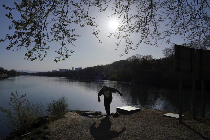 A man walks along the Saone river during a nationwide confinement to counter the COVID-19, on the Barbe island in Lyon, central France, Tuesday, April 7, 2020. The new coronavirus causes mild or moderate symptoms for most people, but for some, especially older adults and people with existing health problems, it can cause more severe illness or death. (AP Photo/Laurent Cipriani)