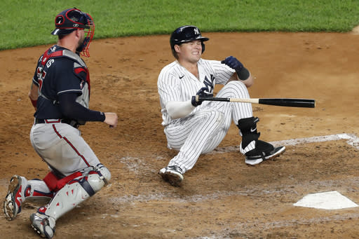 Atlanta Braves catcher Tyler Flowers, left, watches as New York Yankees Luke Voit falls to the dirt after being hit on the hand by a pitch during the fifth inning of a baseball game, Tuesday, Aug. 11, 2020, in New York. Voit was seen by a trainer but stayed in the game. (AP Photo/Kathy Willens)