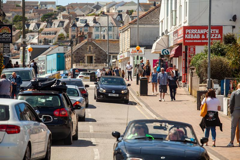 "The Perranporth High Street in Cornwall, busy with visitors. 1st August 2020. See SWNS story SWPLtourism; Cornwall residents fear a local lockdown and say they are ""scared to leave their houses"" - as some of the county's beaches are likened to ""Benidorm on steroids"". Some of the more popular seaside destinations along the south-west coast have seen trails of cars queuing through the town as visitors flock to beaches or holiday parks in search of a 'staycation'. But locals in these popular towns have been left feeling ""uneasy"" about leaving their homes - and some fear they could be in for a local lockdown set to be worse than the first lockdown. Tina-Marie Lally, from Penzance, tried to visit Porthminster Beach in St Ives last week - but shared photos on Facebook of the beach crowded with people and windbreakers."