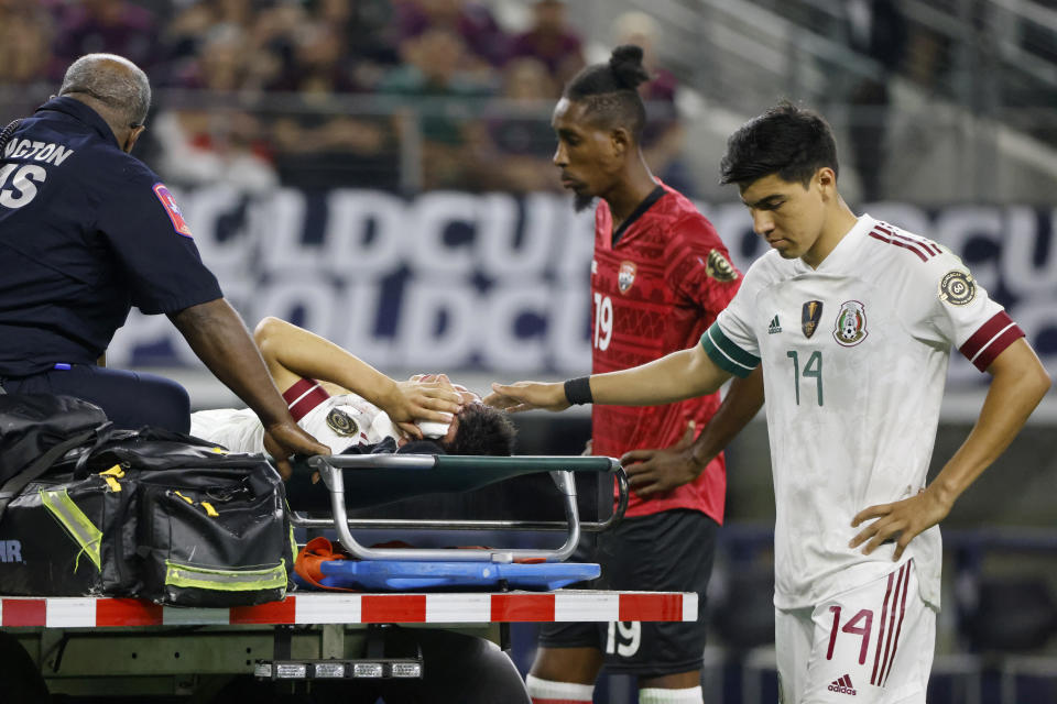 Injured Mexico forward Hirving Lozano, on stretcher, is comforted by Erick Gutierrez (14) as Trinidad and Tobago defender Ross Russell (19) watches during the first half of a CONCACAF Gold Cup Group A soccer match in Arlington, Texas, Saturday, July 10, 2021. (AP Photo/Michael Ainsworth)