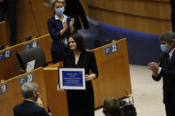 Belarusian opposition politician Sviatlana Tsikhanouskaya, center, is applauded as holds her prize during the Sakharov Prize ceremony at the European Parliament in Brussels, Wednesday, Dec. 16, 2020. The European Union has awarded its top human rights prize to the Belarusian democratic opposition. (AP Photo/Francisco Seco)