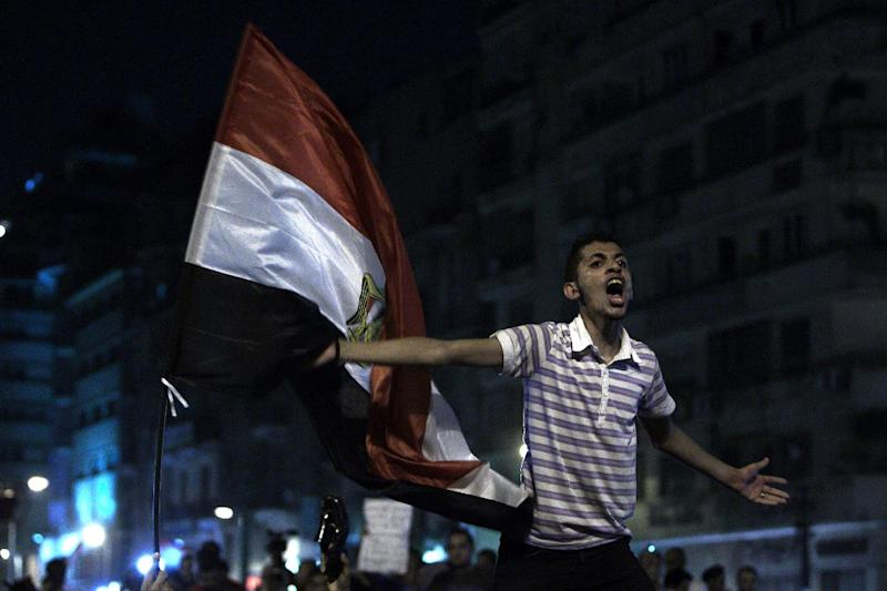 A youth shouts next to an Egyptian flag as the revolutionary youth of Egypt return to Tahrir to protest the outcome of the Egyptian presidential election, Cairo, Egypt, May 28, 2012. The runoff vote for Egypt's next president will pit the Muslim Brotherhood's candidate against the last prime minister to serve under Hosni Mubarak, according to full official results released Monday by the election commission. Commission chief Farouq Sultan told a news conference that the Brotherhood's Mohammed Morsi and Ahmed Shafiq, a former air force commander and a longtime friend of the ousted leader, were the top two finishers in the first round of voting held on May 23-24. (AP Photo/Fredrik Persson)