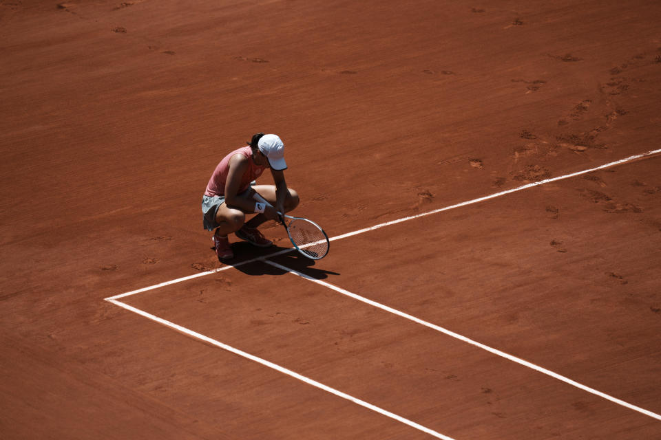 Poland's Iga Swiątek kneels on the court as she plays Maria Sakkari of Greece during their quarterfinal match of the French Open tennis tournament at the Roland Garros stadium Wednesday, June 9, 2021 in Paris. (AP Photo/Thibault Camus)