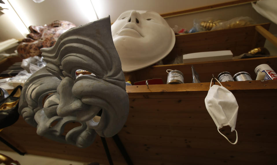 A sanitary face mask hangs next to carnival mask in an artisan workshop in Venice, Italy, Saturday, Jan. 30, 2021. In another year, masks would be an accepted sign of gaiety in Venice, an accessory worn for games, parties and crowds. Since the onset of the COVID-19 pandemic face masks are worn now to protect, not amuse. (AP Photo/Antonio Calanni)