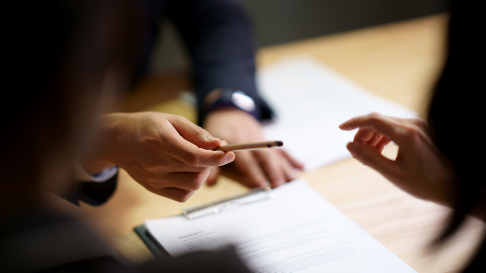 A person passes a pen to another to sign a contract