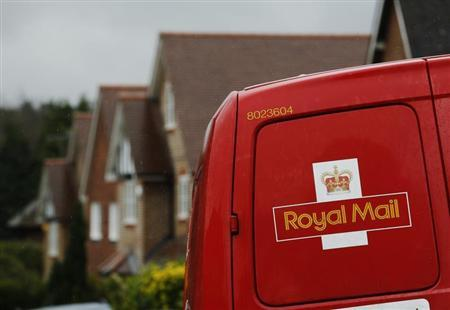 A Royal Mail postal van is parked outside homes in Maybury near Woking in southern England