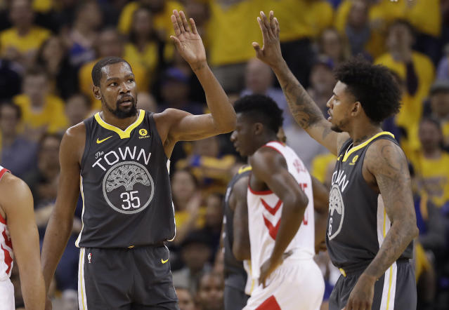 Golden State Warriors forward Kevin Durant (35) celebrates with guard Nick Young during the first half of Game 4 of the NBA basketball Western Conference Finals against the Houston Rockets in Oakland, Calif., Tuesday, May 22, 2018. (AP Photo/Marcio Jose Sanchez)