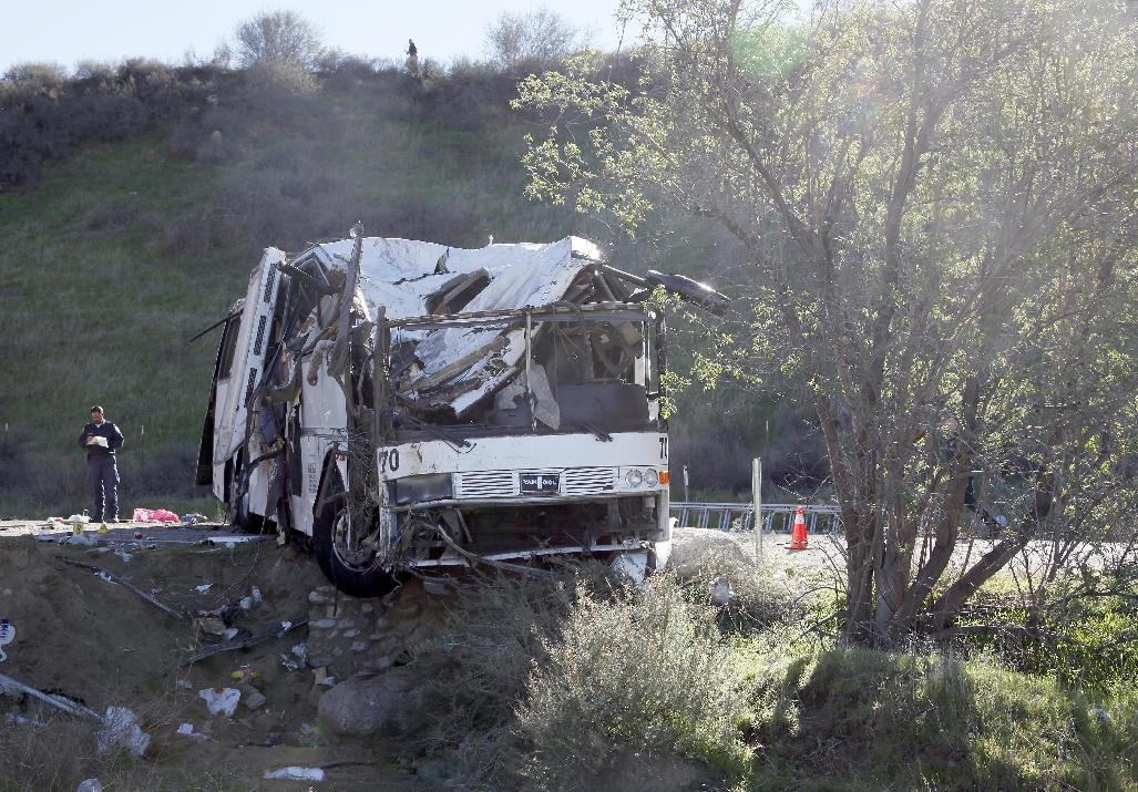 An official takes notes Monday Feb. 4, 2013, at the scene of a tour bus crash near San Bernardino, Calif. The tour bus carrying dozens of men, women and children from Tijuana, Mexico, crashed in the mountains of Southern California killing at least eight people, authorities said. ( AP Photo/Nick Ut)