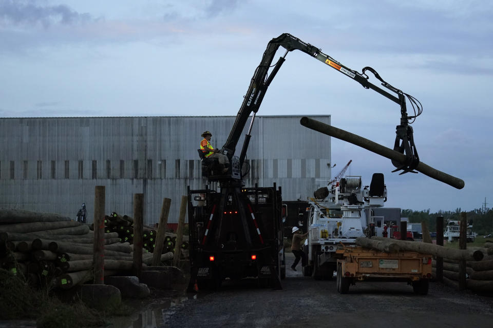 Utility poles are loaded onto trucks at dawn before heading out to restore power, at a tent city for electrical workers in Amelia, La., Friday, Sept. 17, 2021. In the wake of hurricanes, one of the most common and comforting sites is the thousands of electric workers who flow into a battered region when the winds die down to restore power and a sense of normalcy. (AP Photo/Gerald Herbert)