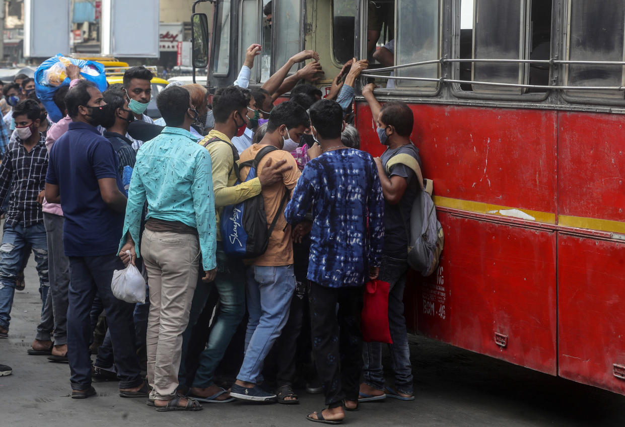 People wearing masks board a bus in Mumbai, India, Monday, April 5, 2021. India reported its biggest single-day spike in confirmed coronavirus cases since the pandemic began Monday, and officials in the hard-hit state home to Mumbai are returning to the closure of some businesses and places of worship in a bid to slow the spread. (AP Photo/Rafiq Maqbool)