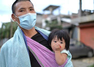 A man wearing a face mask walks with an infant on a sling in Imphal, India, Thursday, June 17, 2021. (AP Photo/Yirmiyan Arthur)